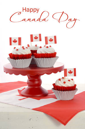 Happy Canada Day celebration cupcakes with red and white maple leaf flag on red cake stand against a white background, vertical with sample text.