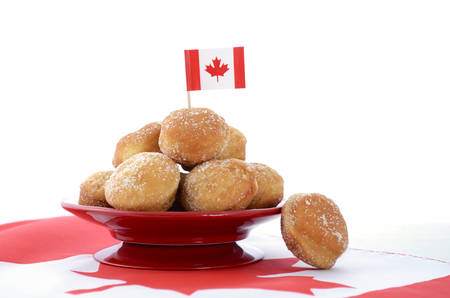 Stack of donut holes on red plate on Canadian maple leaf flag for Happy Canada Day celebration party.