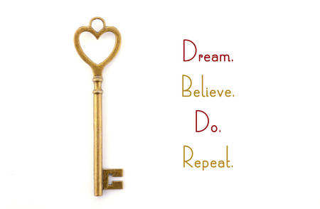 Gold heart shape key with inspirational phrase, dream believe do repeat.