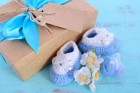 Photo pour Baby shower Its a Boy natural wrap gift with gift box, baby booties and dummy on pale blue shabby chic rustic wood table. - image libre de droit