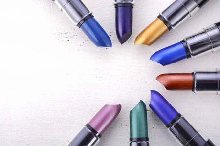 Photo pour Modern makeup lipstick color range with green, purple, blue, gold, and bronze lipsticks on white wood table background. - image libre de droit