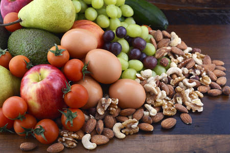 Foto de Healthy Diet with fresh fruit, apples, pears, avocados, grapes, eggs, nuts, tomatoes cucumbers on a rustic wood background. - Imagen libre de derechos
