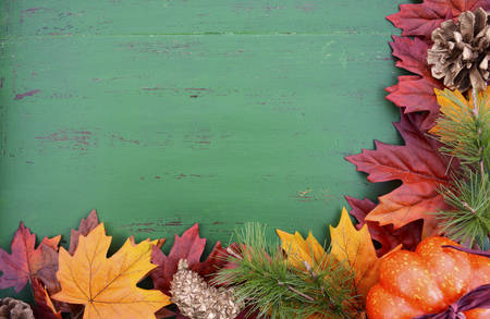 Autumn Fall rustic background on green vintage distressed wood with autumn leaves and decorations.