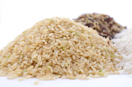 Stacks of raw gluten-free rice cereal ingredient, including white, brown, red and black rice grains on white table and background, with focus on brown rice.