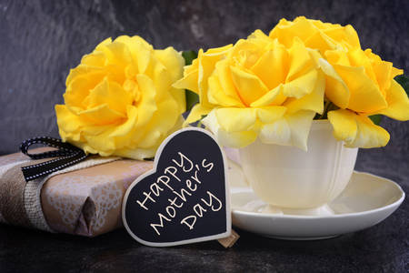 HAppy Mothers Day gift of yellow roses in vintage style china tea cup on black slate background.