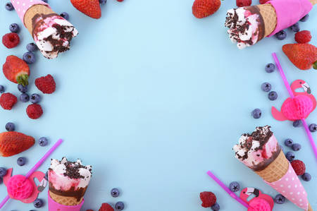 Pink and blue theme Summertime background with decorated borders of ice creams and berries on wood background.