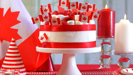 Canada Day national holiday celebration party table with  cake and flags.