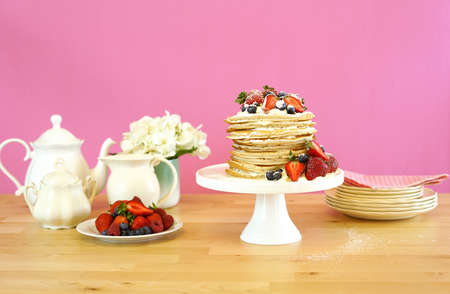 Photo for Shrove Pancake Tuesday, last day before Lent, stack of pancakes cake prepared with layers of whipped cream and fresh berries. - Royalty Free Image