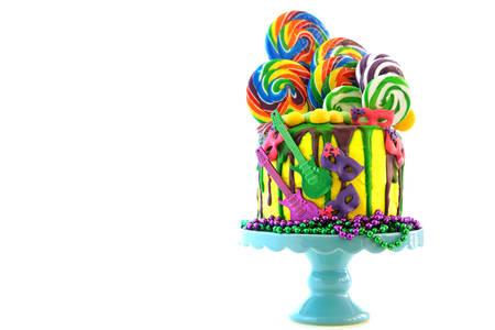 Photo for Mardi Gras theme on-trend candy land fantasy drip cake on white - Royalty Free Image