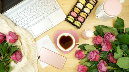 Photo pour Feminine desk or workspace coffee break time overhead flatlay with modern hi tech laptop and scattered roses. - image libre de droit