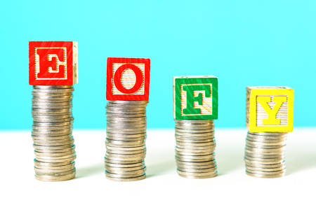 Photo pour End of Financial Year and savings concept stacking coins with EOFY building blocks. - image libre de droit
