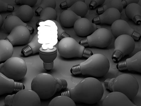 It s time for energy saving light bulb, one glowing compact fluorescent light bulb standing out from the unlit incandescent bulbs