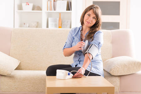 Beautiful woman checking her blood pressure at home