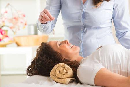 Alternative medicine therapist using pendulum to make a diagnosis