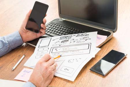 Photo pour Designer working at new mobile applications - image libre de droit