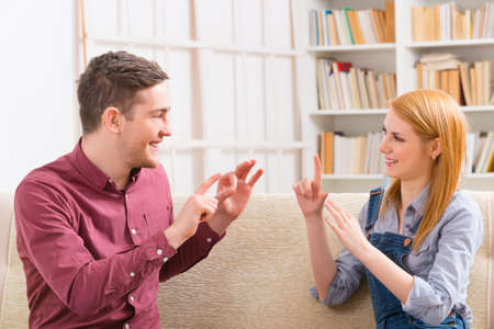 Photo pour Smiling young woman talking using sign language with her hearing impairment man - image libre de droit