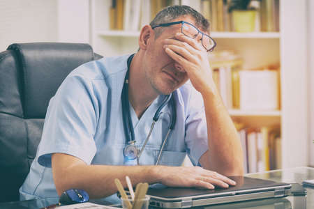 Photo pour Overworked doctor sitting in his office - image libre de droit
