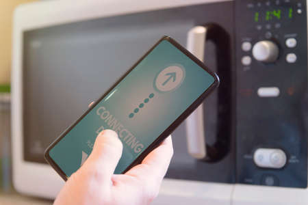 Connecting microwave oven with smart phone. Smart home and Internet of Things IoT concept
