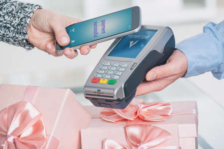 Making contactless payment with smart phone over payment terminal at shop