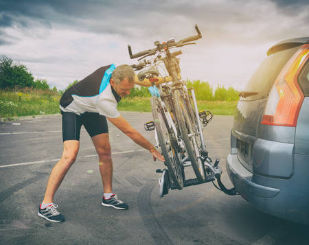 Photo pour Man wearing sportswear loading bicycles on the bike rack mounted to a car towbar - image libre de droit