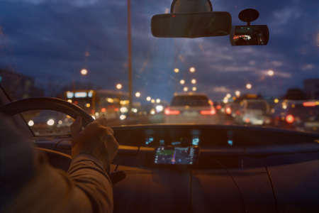 Foto de Driving a car in the city at night in traffic jams. the concept of a difficult return home - Imagen libre de derechos