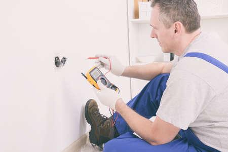 Photo pour Electrician checking socket voltage with digital multimeter - image libre de droit