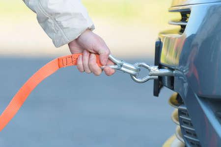 Photo pour Woman assembling towing line to a broken car - image libre de droit