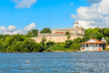 Jagua castle fortified walls with trees and fishing boats in the foreground, Cienfuegos province, Cuba