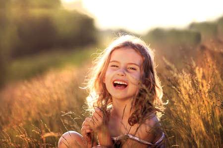 Photo pour Adorable little girl laughing in a meadow - happy girl - image libre de droit