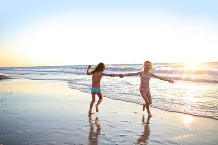 Foto de Two sisters dancing on the beach at sunset - Imagen libre de derechos
