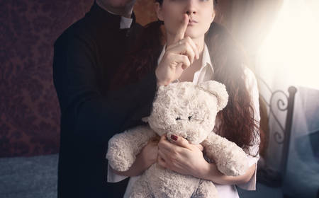 Photo pour priest is holding a thumb on the lips of a young girl - image libre de droit