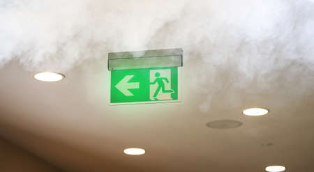 Photo pour Evacuating sign in office builging while fire - image libre de droit