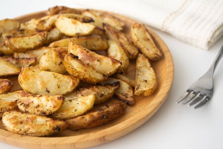 Photo pour Oven baked potato wedges with dried herbs on a wooden plate with a napkin and a fork in the background - image libre de droit