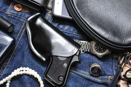 A woman s purse and gun and accessories