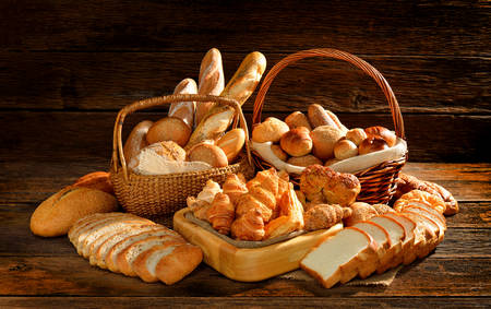 Bread and rolls in wicker basket on old wooden