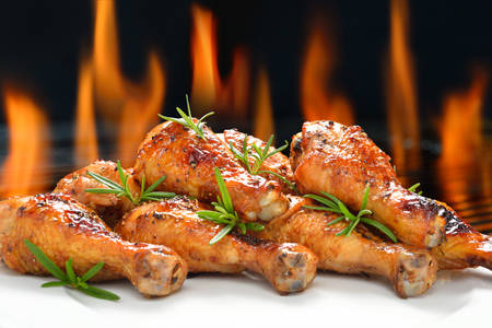 Grilled chicken legs on white plate