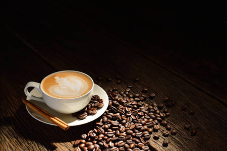Photo for Cup of cafe latte and coffee beans on old wooden background - Royalty Free Image