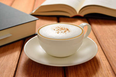 Cup of cappuccino coffee and books on wooden table
