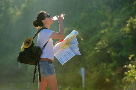 Foto de Woman tourist with backpack drinking water in nature - Imagen libre de derechos