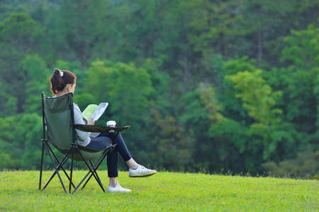 Young woman sitting on camping chair reading a book in the park