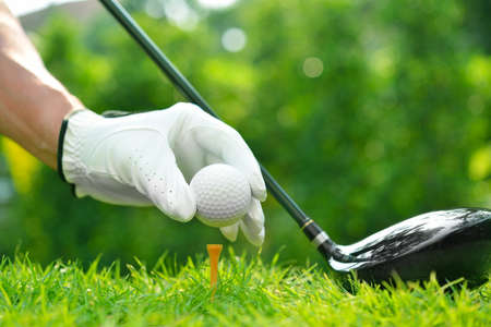 Photo pour Golfer's hand holding golf ball with driver on green grass with golf course background - image libre de droit