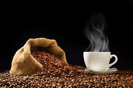 Cup of coffee with smoke and coffee beans in burlap sack on black background