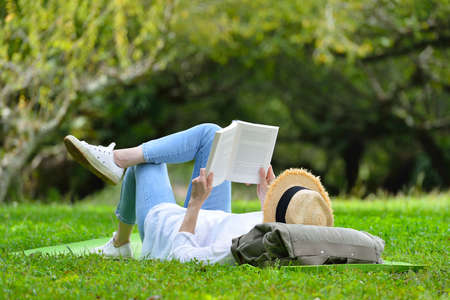 Happy woman lying on green grass reading a book in the park( outdoors )