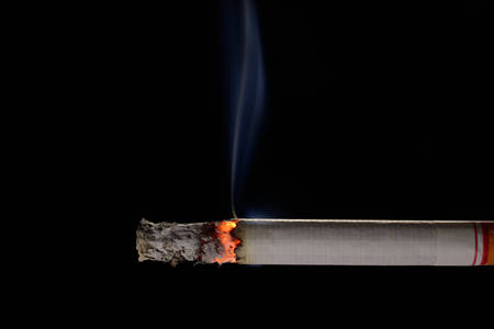 Photo for Lit and burning cigarette with smoke on black background - Royalty Free Image
