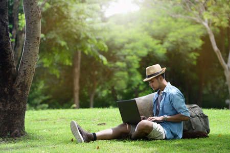 Photo pour Young man traveling and working on laptop in the park - image libre de droit