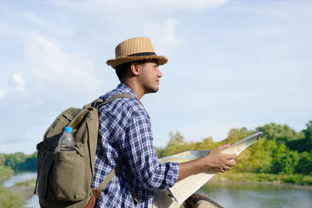 Photo pour Young Asian tourist man with backpack and map looking at the nature - image libre de droit