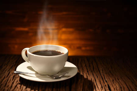 Photo pour Cup of coffee with smoke on old wooden background - image libre de droit