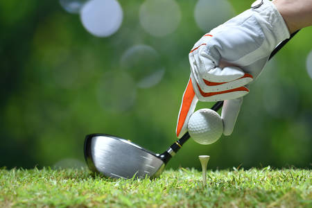 Photo pour Hand hold golf ball with tee on golf course - image libre de droit