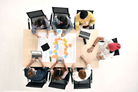 Top view of group of young businesspersons having discussion and sharing opinions in meeting at office