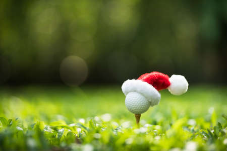 Photo for Festive-looking golf ball on tee with Santa Claus' hat on top for holiday season on golf couse backgroubd - Royalty Free Image